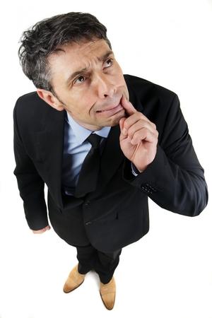 Hoge hoek volledige lengte portret van een doordachte fronsen zakenman staand zoekt met zijn vinger naar zijn mond als hij probeert om te onthouden een vergeten feit of het vinden van een oplossing, op wit