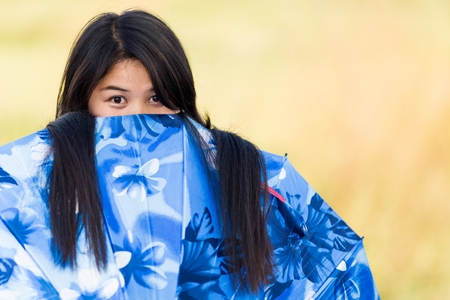 tantalising: Playful young Thai girl peeking over the top of her blue umbrella