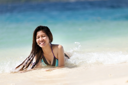 Attractive young Filipina woman swimming in the sea laughing as she lies in the shallow surf enjoying the summer sunshine photo