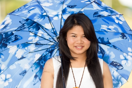 sun umbrella: Beautiful young Thai girl under a blue sunshade or umbrella to protect her against the hot summer sun smiling happily at the camera