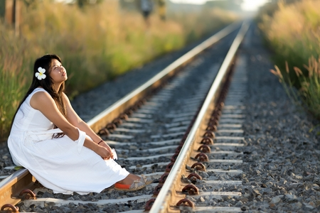 receding: Beautiful young Thai woman meditating sitting in the last rays of the sun on a receding train track