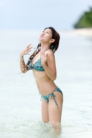 tilted: Young woman in a bikini splashing in the sea spraying droplets of water over her body as she stands with her head tilted back in enjoyment