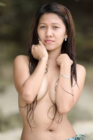 Beautiful serious young Asian woman standing with her arms raised to conceal her breasts looking thoughtfully at the camera photo