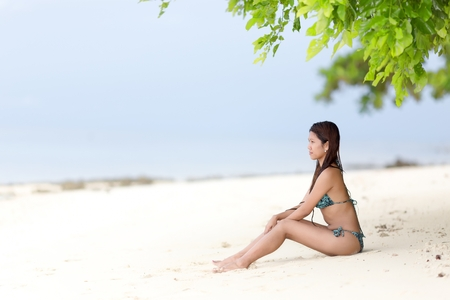 Beautiful Filipina woman sitting in her bikini on a tropical beach in her bikini on the golden sand in the shade of a green leafy tree looking out towards the ocean, with copyspace photo
