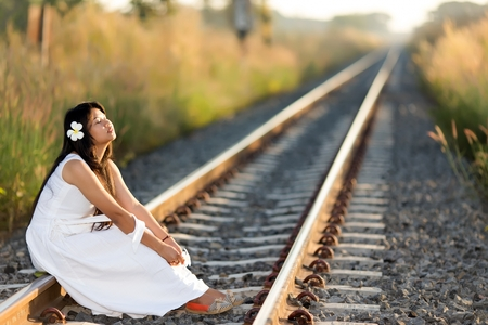 receding: Beautiful young Thai woman meditating sitting in the last rays of the sun on a receding train track in a fresh white dress with a serene expression and her face lifted to the light