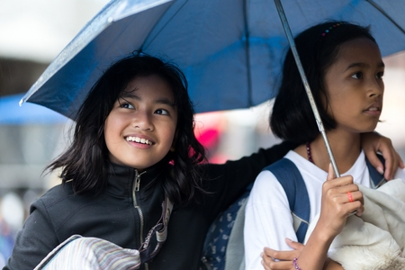 sheltering: BANAUE, PHILIPPINES, DECEMBER 03:Two Filipina girls sheltering under an umbrella together as they walk down an urban street in village of Banaue, north Luzon, Philippines, on december 03, 2013