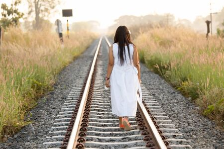 Young woman walking away from the camera down a rural railway track bordered by long grass in a white dress on a summer evening photo