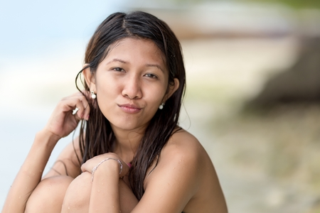 knees bent: Beautiful charismatic young Filipina woman sitting with her knees bent up to her chin on a beach looking at the camera with a gentle wry smile