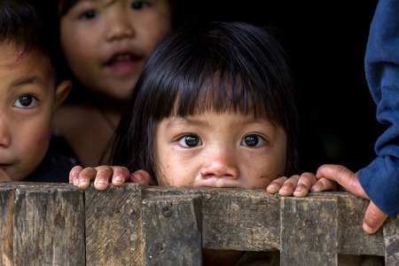 BANAUE, Filippijnen 04 december: Een jonge niet-geïdentificeerde Filipijns meisje met haar broers en zussen is staren naar de camera in het dorp van Banaue, noord Luzon, Filippijnen, op 4 december 2013