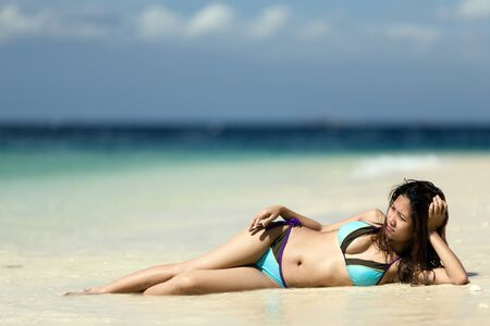 Filipina woman lying on the seashore photo