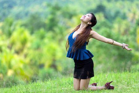 mujer arrodillada: Bella y elegante mujer filipina regocijo en la naturaleza de rodillas en la hierba verde en el campo con la cabeza hacia atrás y los brazos extendidos en la luz del sol con una sonrisa alegre Foto de archivo