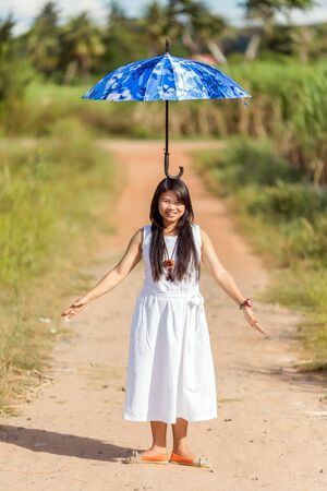 feat: Beautiful young Thai girl balancing an open blue umbrella on her head as she stands on a rural path in the summer sunshine with a lovely smile and her arms outspread