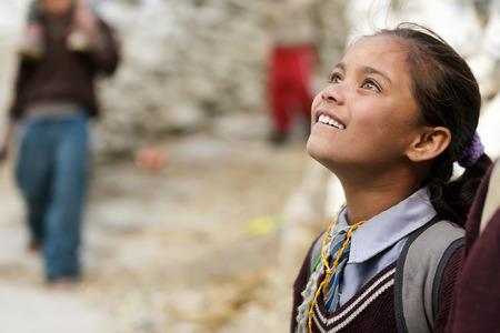 MUKTINAH, NEPAL, 10 november: een klein meisje komt terug van school is op zoek naar haar vrienden met een bewonderende uitdrukking in Muktinah dorp, Annapurna, Nepal op 10 november 2010