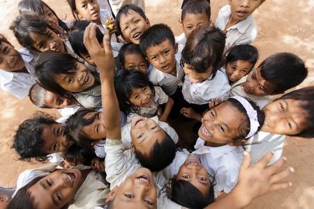 2012 年 12 月 4 日シェムリ アップ、カンボジアでの校庭でポーズをとってうれしそうな子供のシェムリ アップ-12 月 04日: グループ 報道画像