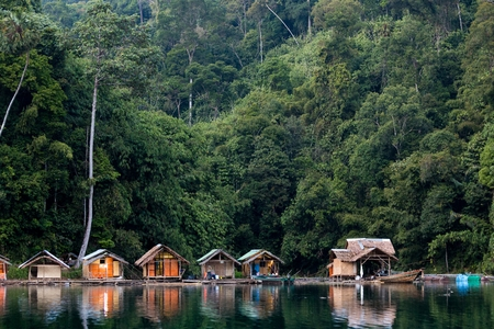 Wooden bungalows on tropical shore in the Chiew Lan Lake, Khao Sok national park, Thailand photo