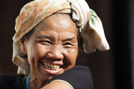 BAM MUANG PAM, THAILAND, NOVEMBER 22 : close portrait of a mature Karen tribe woman laughing, Thai ethnicity, in the village of  Bam Muang Pam, north Thailand on November 22, 2012