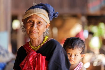 third age: BAM MUANG PAM, THAILAND, NOVEMBER 22 : close portrait of an old Karen tribe woman with his grandson, Thai ethnicity, in the village of  Bam Muang Pam, north Thailand on November 22, 2012 Editorial
