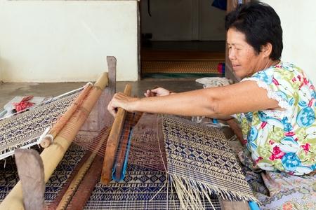 straw mat: Thai woman weaving traditional straw mat using Cyperus alternifolius stems, Khon Kaen, Thailand Stock Photo