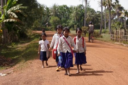 Siem Reap, Kambodscha, 04 Dezember: Kambodschanisches Mädchen Studenten in traditioneller Kleidung zu Fuß auf einer Landstraße in der Nähe Schmutz Siem Reap, Kambodscha am 4. Dezember 2012 Standard-Bild - 30373873