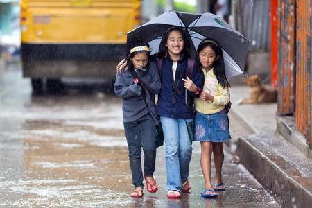 BANAUE, Filipijnen, december 3: Kleine meisjes lopen in de regen beschutten met een paraplu in de straat van Banaue dorp, noord Luzon, Filippijnen, op 3 december 2013