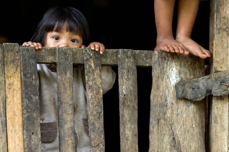 BANAUE, PHILIPPINES, DECEMBER 04 : An unidentified Filipino little girl is staring at the camera behing a wooden fence in the village of Banaue, north Luzon, Philippines, on december 04, 2013