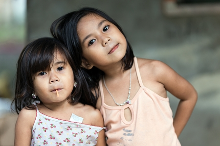 SIQUIJOR ISLAND, PHILIPPINES, DECEMBER 21 : Two unidentified Filipino little girl sisters posing in front of her home in north Siquijor island, Philippines, on december 21, 2013