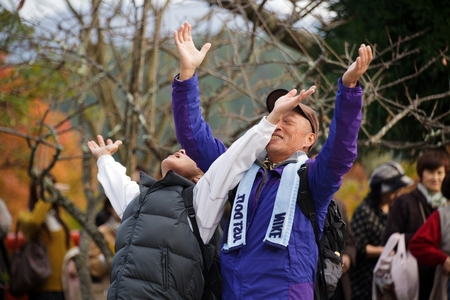 hurting: Kyoto,JAPAN, NOVEMBER 20 : Japanese people stretching our arms in adoration of Shinto gods, the woman is hurting the face of her husband, in Mount Karama, Kyoto, Japan on November 20, 2011 .