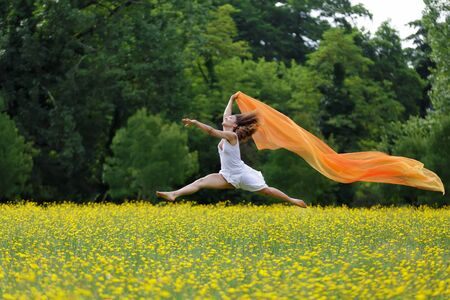 Agile barefoot woman with curly brown hair leaping in the air in a meadow of yellow wildflowers trailing a colorful orange scarf photo