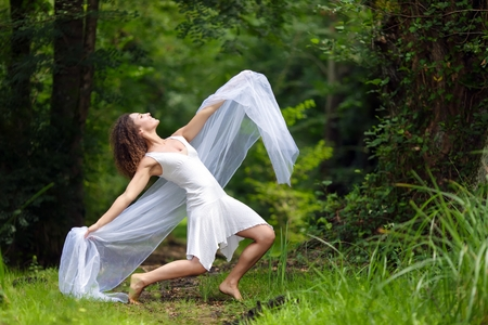 draped: Artistic portrait of a beautiful barefoot woman in a stylish white dress striking a dramatic pose with her outstretched arms draped in filmy white chiffon against a forest backdrop of lush green trees