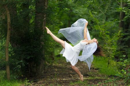 mystical forest: Mystical portrait of a beautiful graceful barefoot woman in a fresh white dress with her arms draped in filmy sheer fabric posing with one leg raised against a lush green woodland backdrop