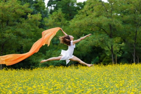 Agile barefoot woman with curly brown hair leaping in the air in a meadow of yellow wildflowers trailing a colorful orange scarf in the breeze as she celebrates her freedom and the beauty of nature photo