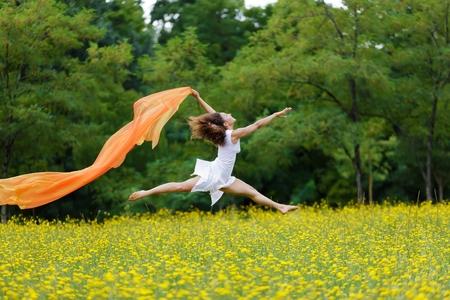 Agile op blote voeten vrouw met krullend bruin haar springen in de lucht in een weide van gele wilde bloemen trailing een kleurrijke oranje sjaal in de wind als ze haar vrijheid en de schoonheid van de natuur viert