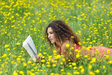 contented: Cute young woman with curly hair lying reading a book in a wildflower meadow full of colorful yellow summer flowers as she relaxes in the tranquility and beauty of nature Stock Photo