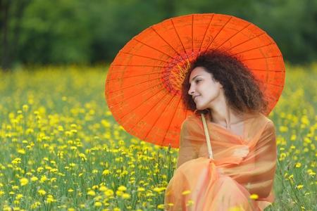 draped: Beautiful elegant woman with an orange asian umbrella draped in a matching chiffon scarf sitting in dandelion summer field Stock Photo