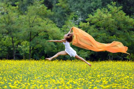 trailing: Agile barefoot woman with curly brown hair leaping in the air in a meadow of yellow wildflowers trailing a colorful orange scarf in the breeze as she celebrates her freedom and the beauty of nature
