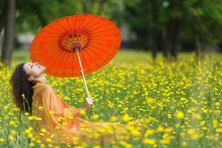Beautiful elegant woman with an orange asian umbrella draped in a matching chiffon scarf sitting in dandelion summer field photo