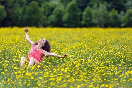 Beautiful young woman stretching her arms high in the air with a smile of pleasure and satisfaction as she sits in a rural meadow full of colorful yellow flowers, with copyspace photo
