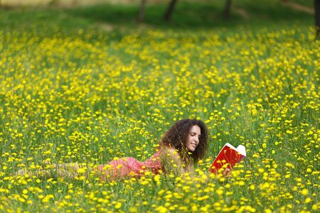 Cute young woman with curly hair lying reading a book in a wildflower meadow full of colorful yellow summer flowers as she relaxes in the tranquility and beauty of nature photo