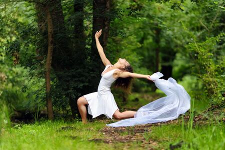 Beautiful barefoot woman in a stylish white dress pose in a forest  of lush green trees photo