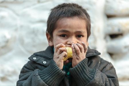 MUKTINAH, NEPAL, 10 novembre 2010: bambino nepalese che mangia una mela nel piccolo villaggio di moutain Muktinah, Annapurna, Nepal.