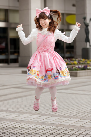 lolita: Happy japanese sweet lolita cosplay jumping on a Tokyo sidewalk Stock Photo
