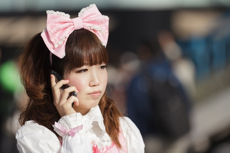 Japanese lolita cosplay woman using her mobile phone in a Tokyo street,, Japan photo