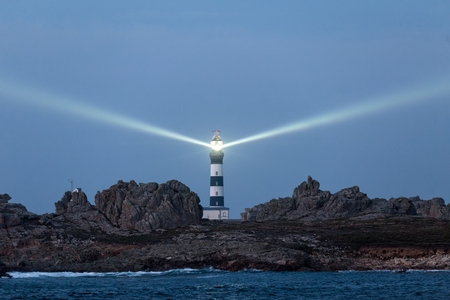 beam: The most powerful lighthouse in the world, illuminated at dusk, Creach point, Brittany, France