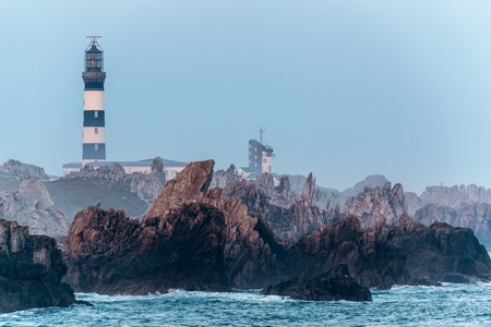 Sharp rocky coastline and Creach lighthouse in the Ushant island, Brittany, France photo