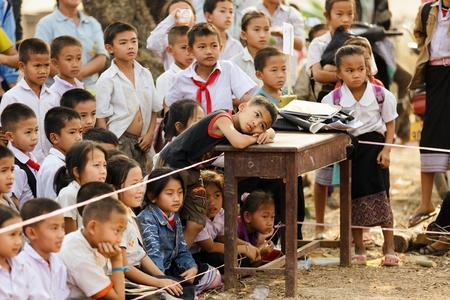 niños pobres: SAYABURY, LAOS, 16 de febrero 2012: la clase de los niños de Laos viendo el espectáculo de teatro al aire libre en el patio del colegio durante el festival Elefantasia en Sayaboury, Laos Editorial