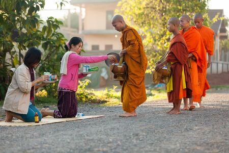 arrodillarse: Vang Vieng, LAOS, 19 de marzo 2011: la mujer que da el alimento diario a los monjes budistas durante limosnas tradicionales de la madrugada en la localidad de Viang Vieng, Laos