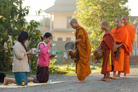limosna: Vang Vieng, LAOS 19 de marzo de 2011: la mujer que da el alimento diario a los monjes budistas durante limosnas tradicionales de la madrugada en la localidad de Viang Vieng, Laos