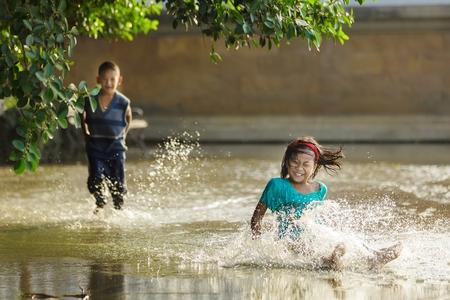 Bangkok, Thailand, 25 december 2011: Gekleed kinderen plezier uitglijden en spetteren in een overstroomd plein in de buurt van de rivier in Bangkok, Thailand