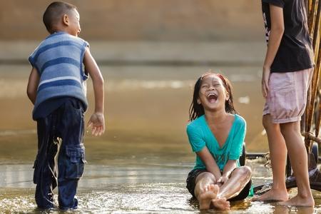 Bangkok, Thaïlande, 25 décembre 2011: Enfants jouant dans un carré inondé près de la rivière et de rire de fort à Bangkok, Thaïlande