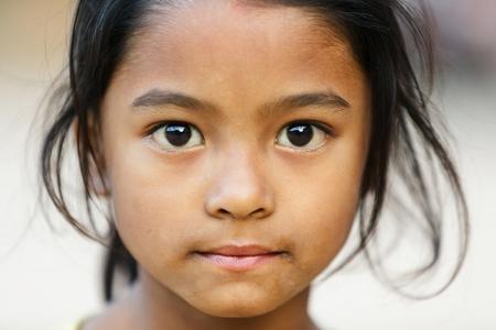 BHAKTAPUR, NEPAL, NOVEMBER 24, 2010: Close portrait of a Nepalese little girl posing in the main Bhaktapur square Editoriali